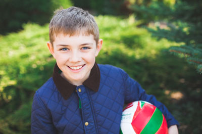 Child with blue eyes holding soccer ball